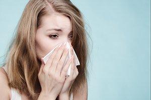 girl sneezing because of allergies